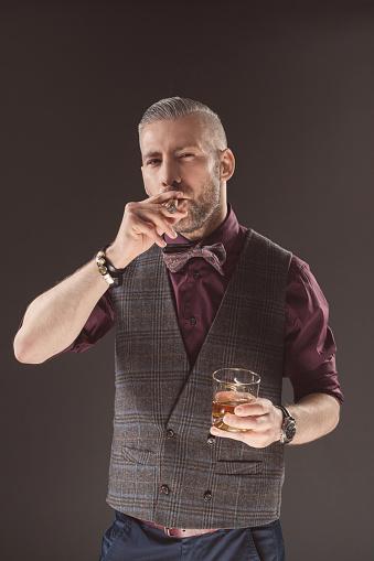 Elegant Man Drinking Scotch Whisky And Smoking Cigar Stock Photo - Download Image Now