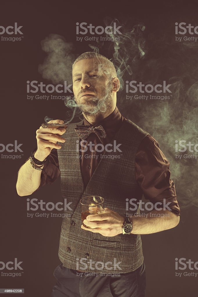 Elegant man drinking scotch whisky and smoking cigar Elegant man wearing tweed vest and bow tie holding glass of whiskey, smoking cigar. Dark tone, black background. 2015 Stock Photo
