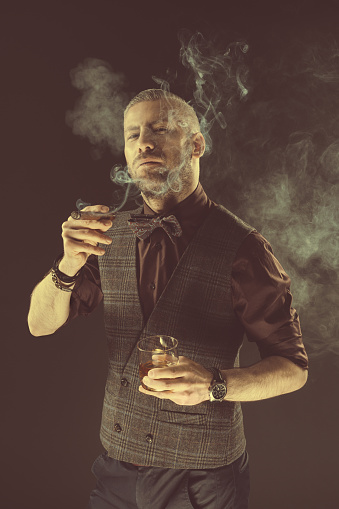 Elegant Man Drinking Scotch Whisky And Smoking Cigar Stock Photo - Download Image Now