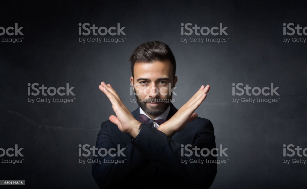 elegant man gesturing x with hands stock photo