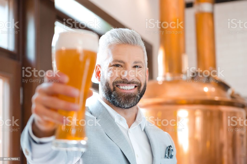 Elegant man holding a beer glass in his microbrewery The microbrewery owner standing in front to copper vat and holding beer glass, smiling at the camera. Adult Stock Photo