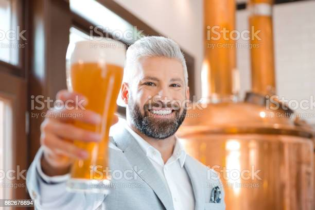 Elegant Man Holding A Beer Glass In His Microbrewery Stock Photo - Download Image Now