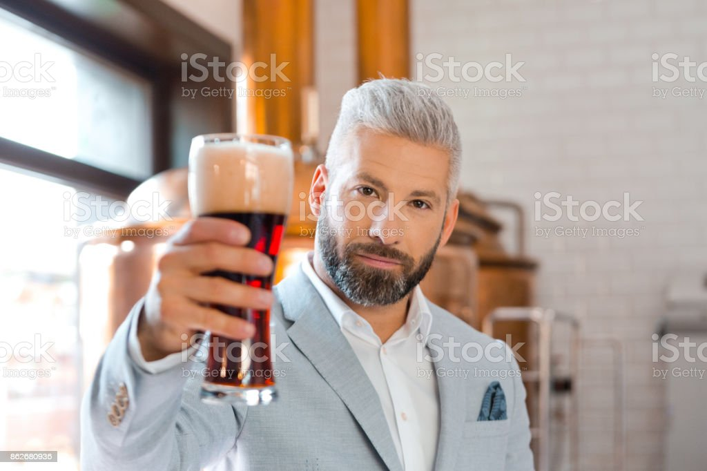 Elegant man holding a beer glass in microbrewery Happy microbrewery owner standing in front to copper vat and holding beer glass, looking at camera. Adult Stock Photo