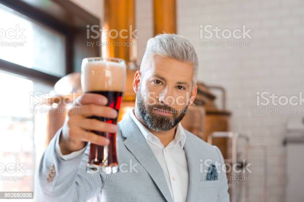 Elegant Man Holding A Beer Glass In Microbrewery Stock Photo - Download Image Now