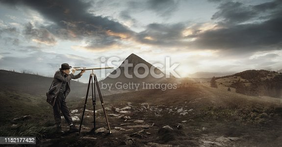Elegant man in classic suit and hat attentively looks through a telescope near by mountain in soft sunset light. A little cloudly sky, forest and green meadows surrounding him in summer evening.