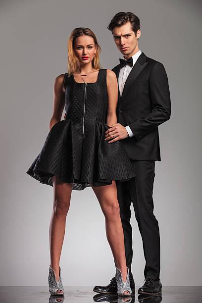 elegant man in tuxedo embracing his woman from behind - knotenkleid stock-fotos und bilder