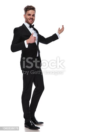 happy elegant man in tuxedo presenting and making the ok thumbs up hand sign on white background