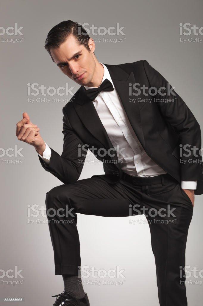 elegant man in tuxedo snapping finger stock photo