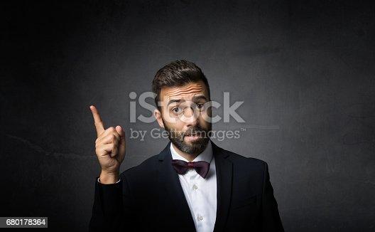 elegant man indicated with finger up, dark background