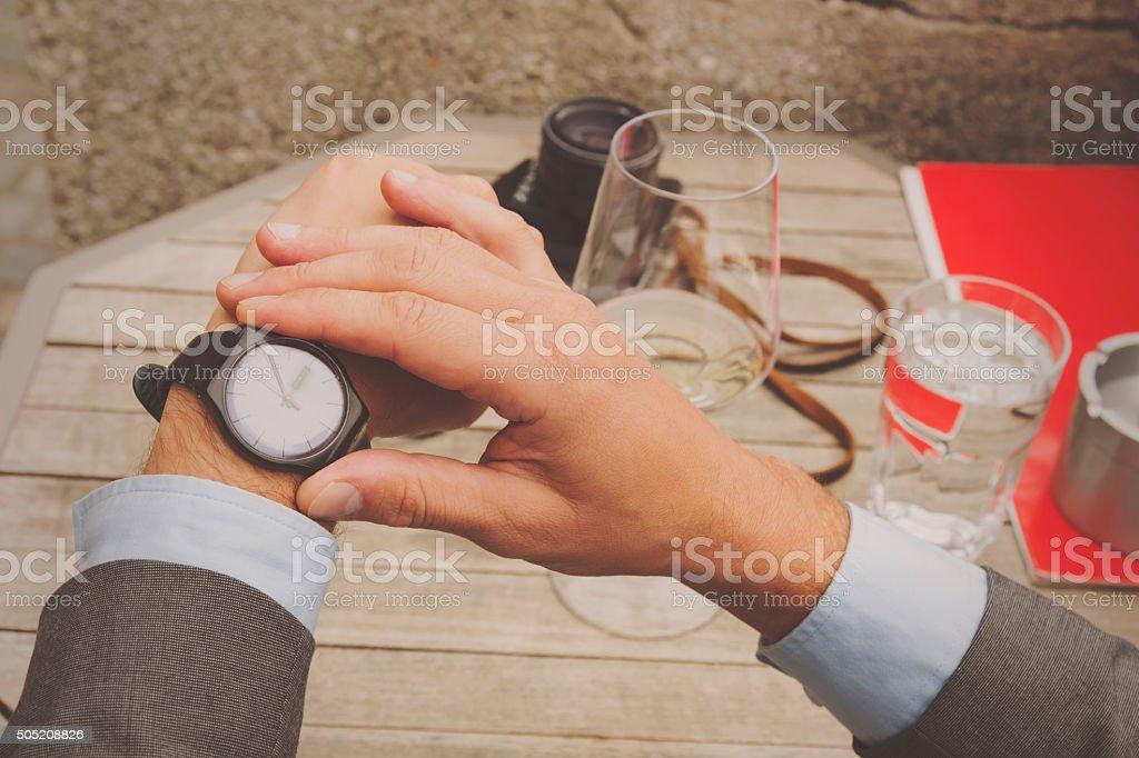 Elegant man looking at his watch. stock photo