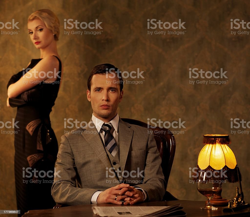 Elegant man on a chair with a woman standing behind him stock photo