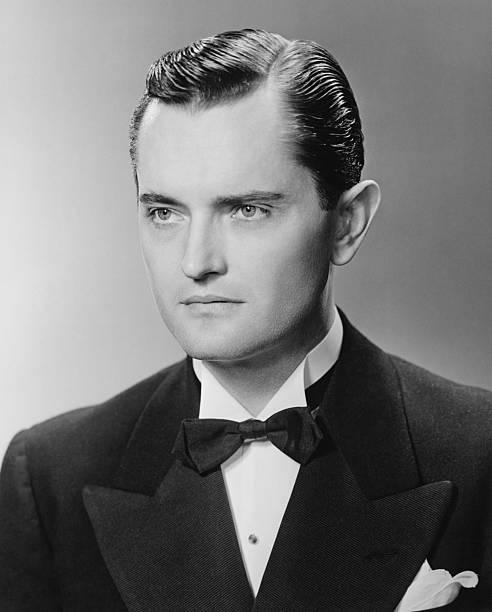 Elegant man posing in studio, (B&W), close-up, portrait stock photo