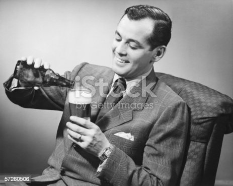istock Elegant man pouring beer from bottle into glass, (B&W) 57260506
