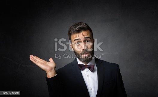 elegant man showing empty space, dark background