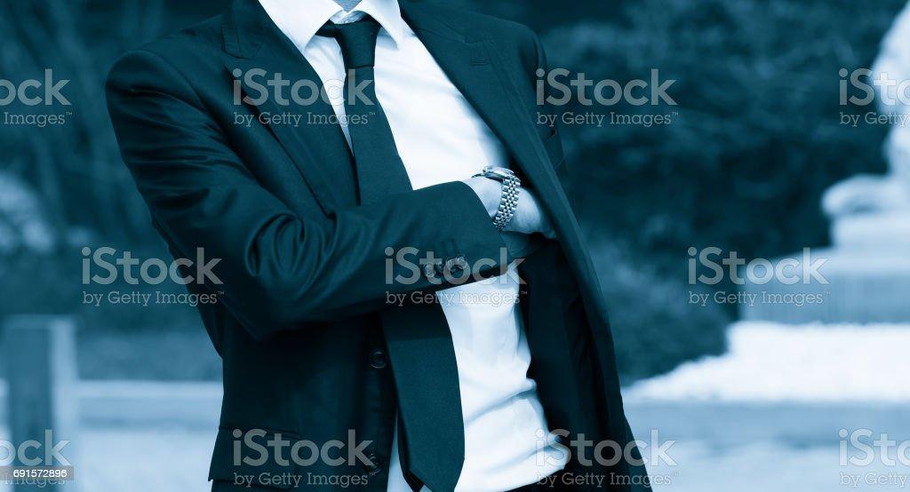 Hombre elegante tomando una pistola de su suite. Concepto de agente secreto. Imagen de tono azul. - foto de stock
