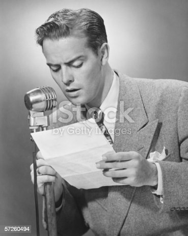 istock Elegant man talking into microphone in studio, (B&W) 57260494