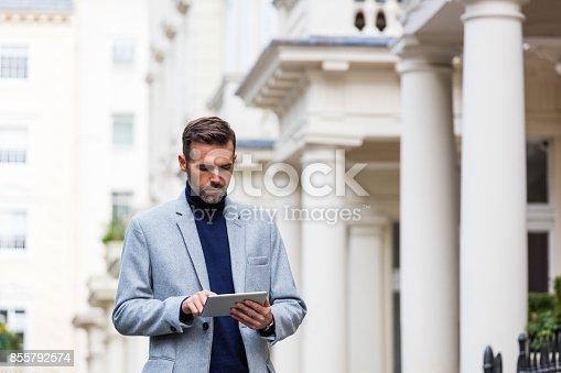 Elegant man wearing grey coat using a digital tablet in front of gregorian houses in London. Autumn season.