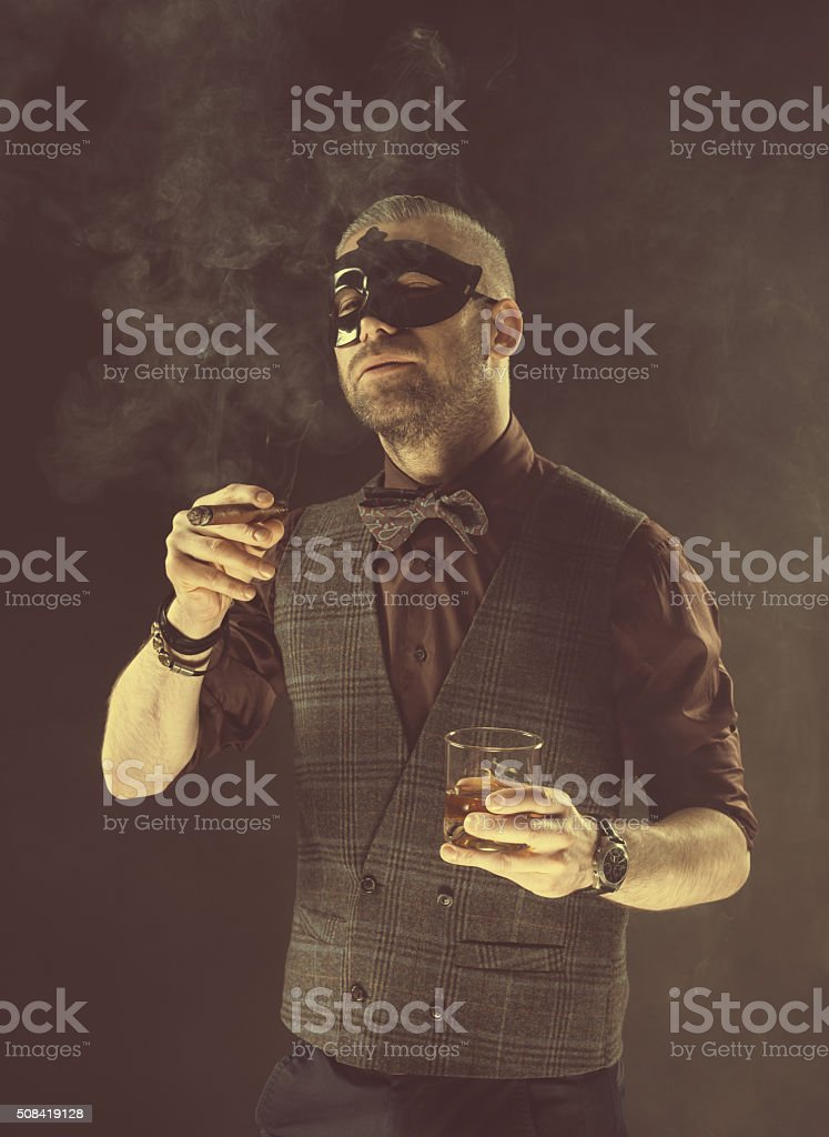 Elegant man wearing carnival mask, drinking whiskey and smoking cigar Elegant man wearing tweed vest, bow tie and carnival mask holding glass of scotch whisky, smoking cigar. Dark tone, black background. Adult Stock Photo