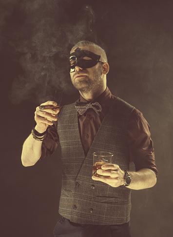 Elegant Man Wearing Carnival Mask Drinking Whiskey And Smoking Cigar Stock Photo - Download Image Now