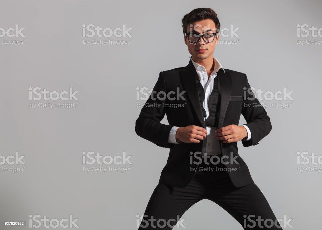 elegant man wearing glasses unbuttoning his tuxedo stock photo