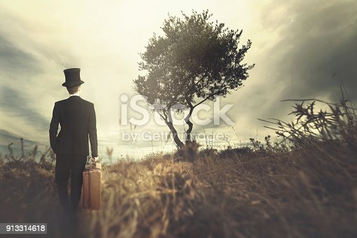 istock elegant man with his suitcase traveling in a surreal place 913314618