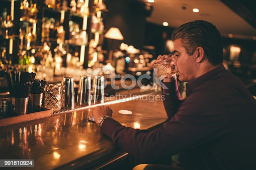 istock Elegant mature man at bar drinking and checking the time 991810924