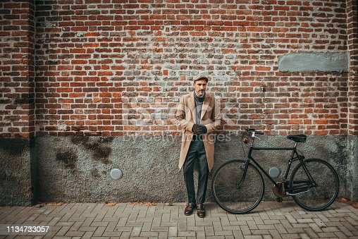 Horizontal photo of elegant mature man leaning to wall next to his bicycle
