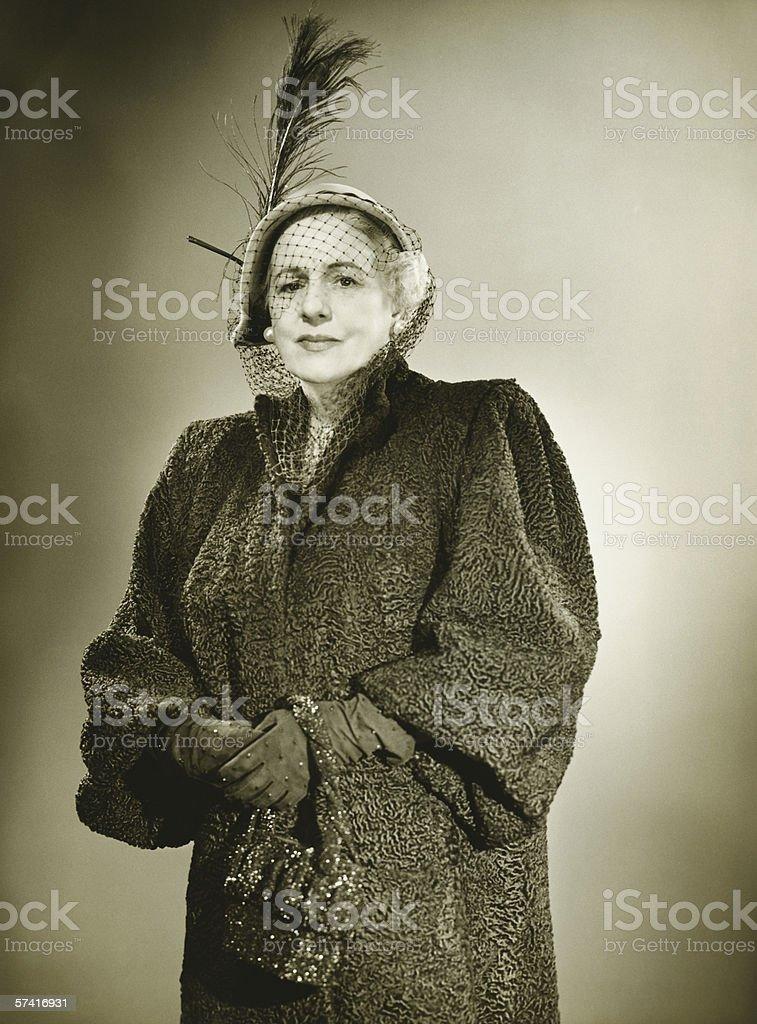 Elegant mature woman in hat and coat posing in studio, (B&W), (Portrait) royalty-free stock photo