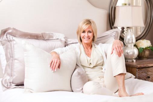 Elegante Reife Frau Ruhen Auf Einem Bett Stockfoto und