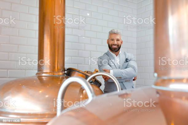 Elegant Microbrewery Owner Standing By Copper Vat Stock Photo - Download Image Now