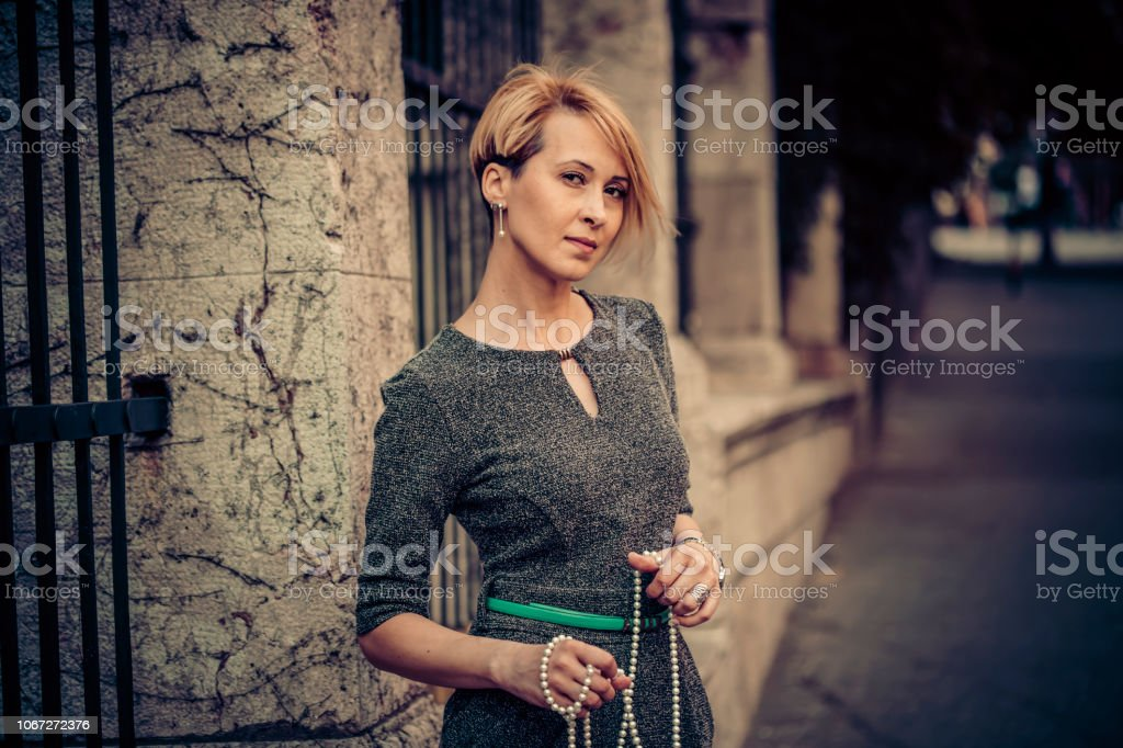 Elegant mid-age woman on the street waiting for someone stock photo