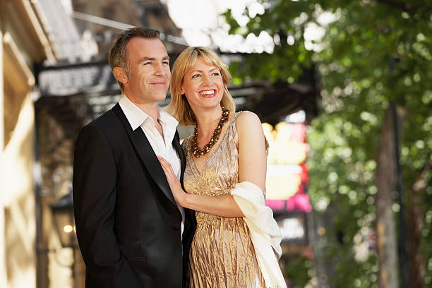 Elegant Middle Aged Couple On London street Elegant middle aged couple outside building on London street evening wear stock pictures, royalty-free photos & images