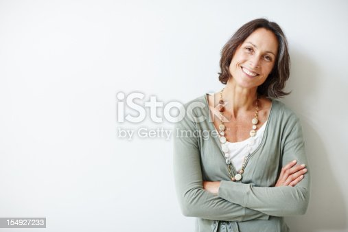 istock Elegant middle aged woman with her arms crossed against white 154927233
