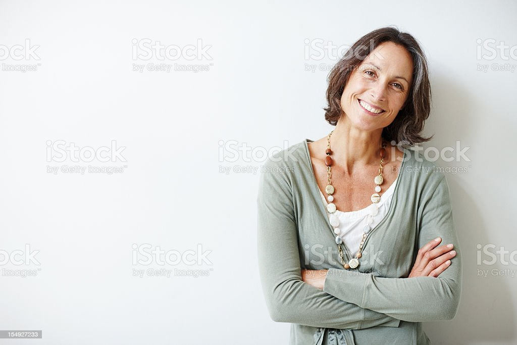 Elegant middle aged woman with her arms crossed against white stock photo