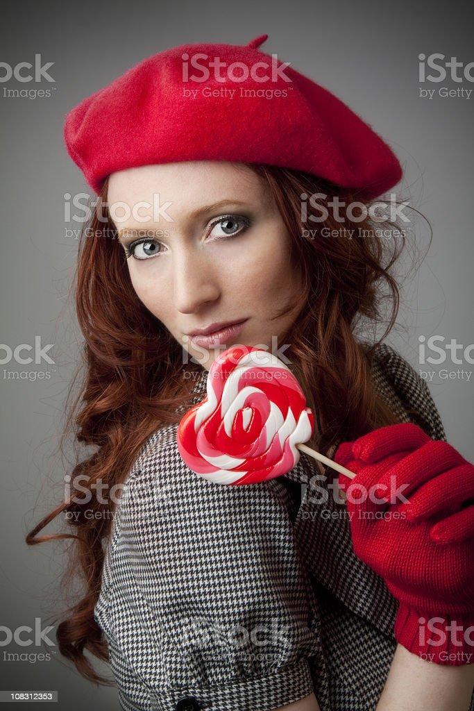 Elegant model wearing red beret with lollipop stock photo