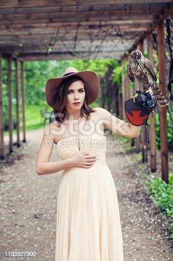 Elegant model woman in hat, outdoor fashion portrait