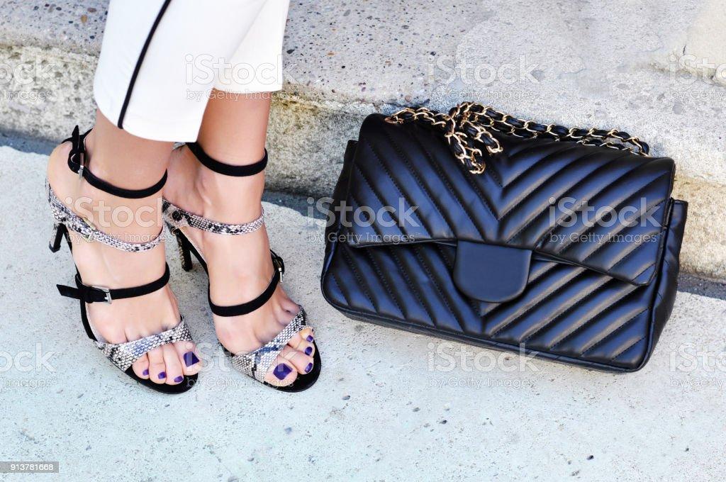 Accesorio de moda moderno elegante de la mujer. Señora blanca vestida con sandalias de tiras de piel de serpiente negro de tacón alto y pantalones blancos con bolso de cuero negro. Las uñas de mujer son ultra violeta - foto de stock