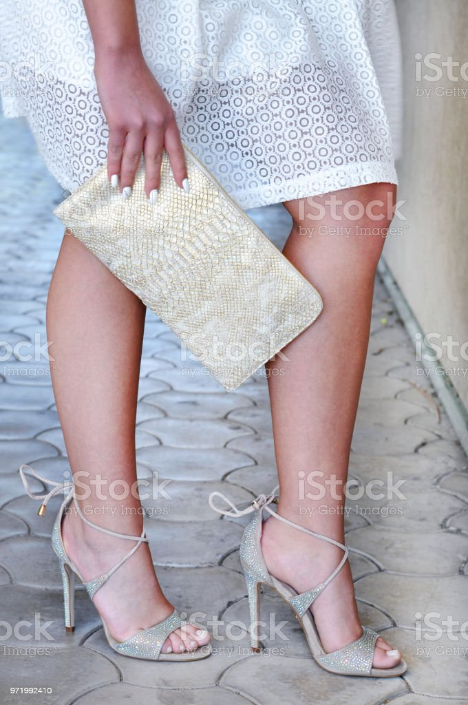 220c2fe9d Caucasian lady wearing high heel strappy sandals and white dress holding  golden leather purse. Fashion concept