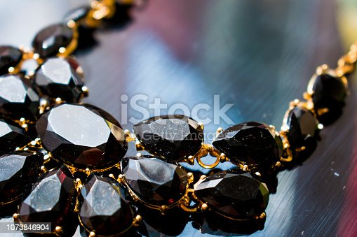 Elegant necklace with black stones and a Golden metal base on a reflective black mirror surface. Dark precious stones in the form of droplets and ovals. Jewelry and accessories for women, fashion background for design.