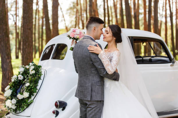 Elegant newlyweds, groom in grey suit and bride in wedding dress with long sleeves and long veil looking at each other near white Just Married car stock photo