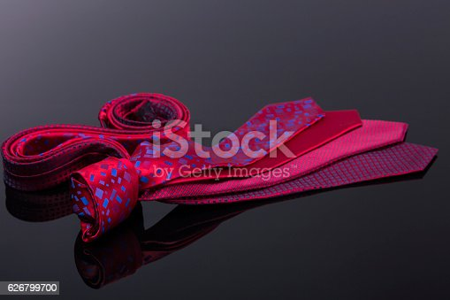 silk ties in different colors, spread out on a black tabl