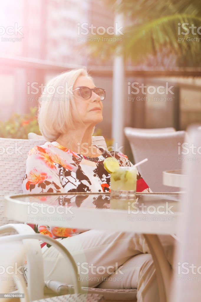 Elegant old lady drinking a caipirinha stock photo