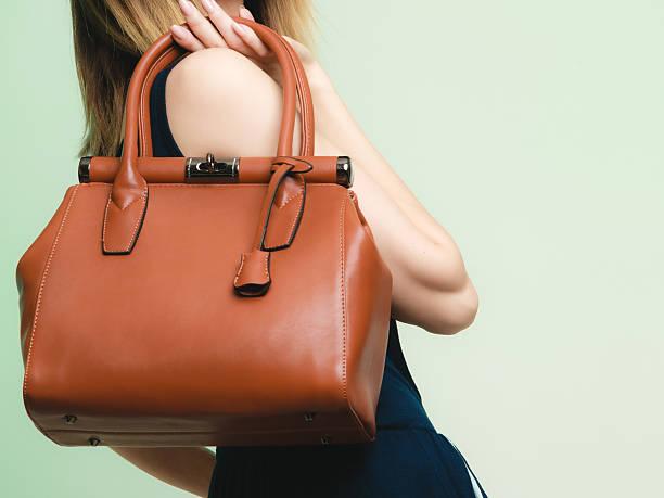 elegantes outfit.  braun ledertasche in weibliche hand - leder handtaschen damen stock-fotos und bilder