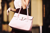 Elegant outfit. Closeup. Leather bag in hands of stylish woman