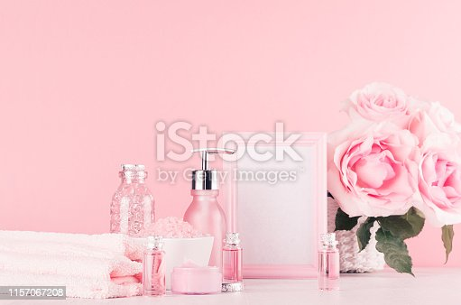 1056636898 istock photo Elegant pink skin, body care products - cream, rose oil, liquid soap, salt, cotton towel - cosmetic accessories, romantic flowers, blank frame  on white wood table. 1157067208