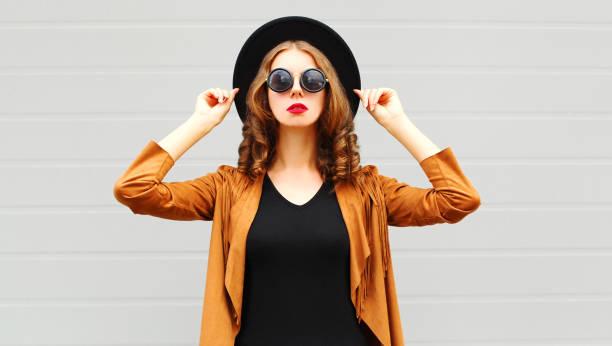 elegante schöne frau trägt einen schwarzen hut, sonnenbrille und jacke über urbane grauen hintergrund - bedruckte leggings stock-fotos und bilder