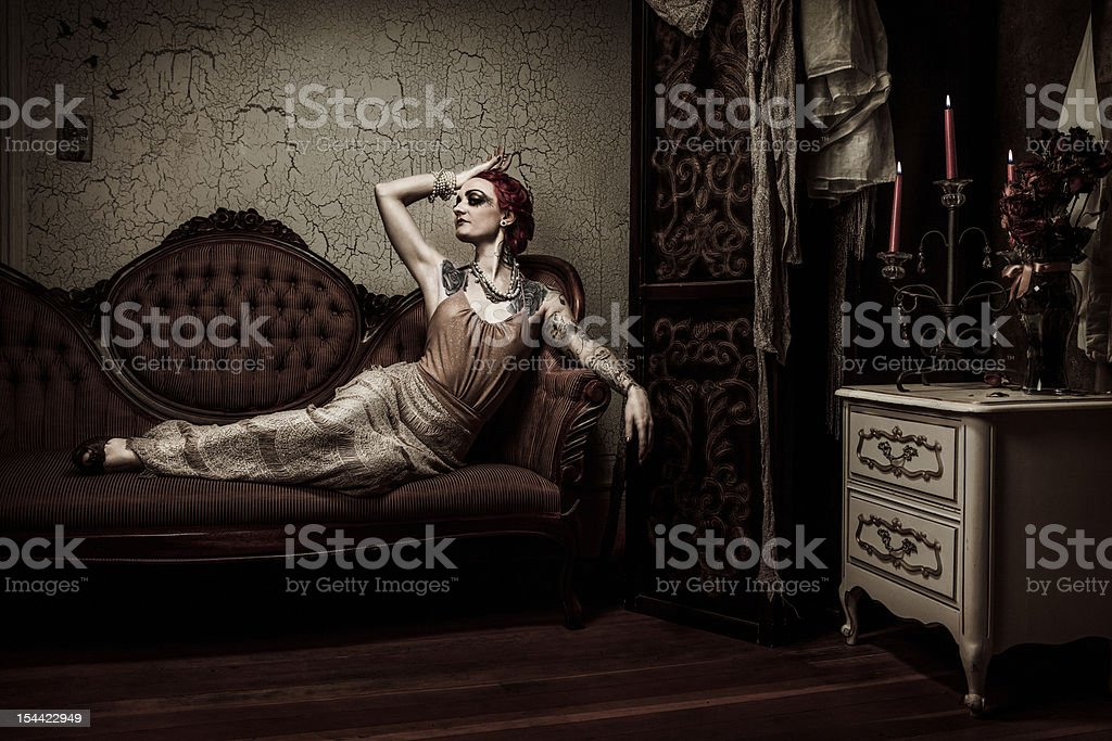 Elegant Retro Woman Lounging on Couch stock photo
