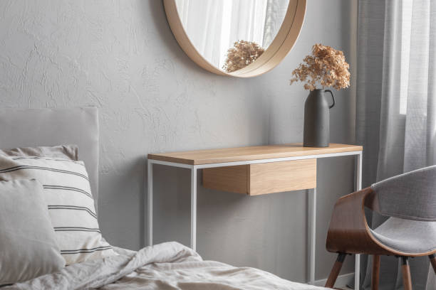 Elegant round mirror in wooden frame above fancy console table with flowers in vase in trendy bedroom interior with beige vase stock photo