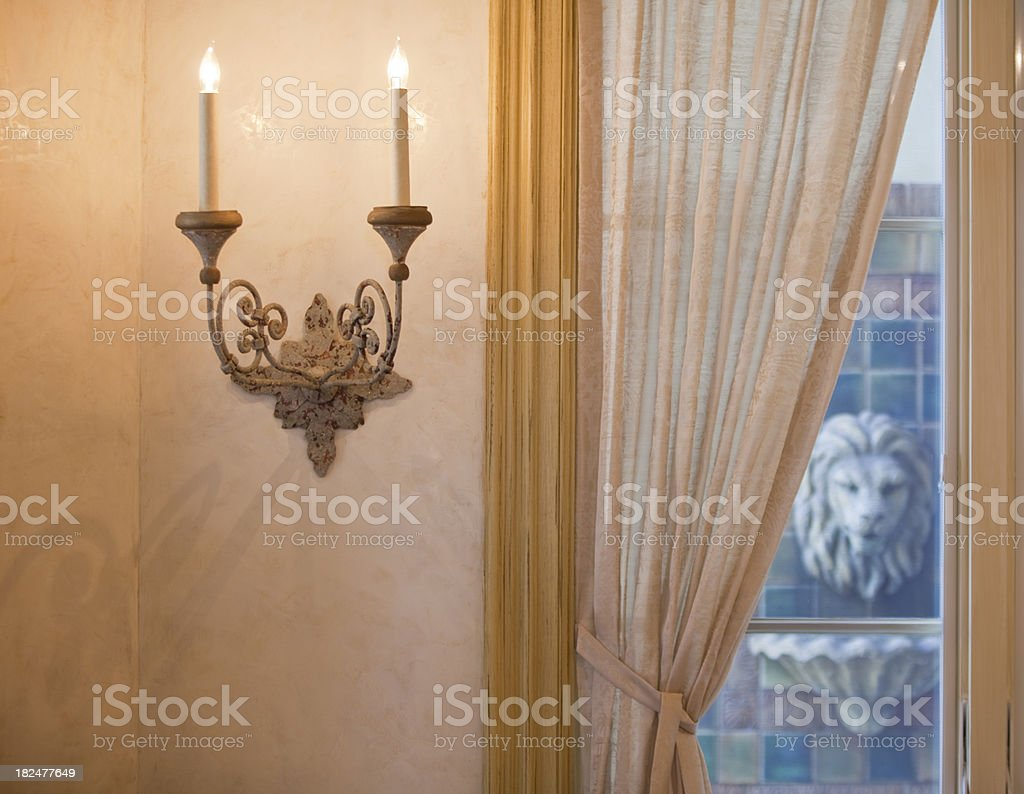 Elegant Sconce on Polished Plaster Wall with Fountain in Window stock photo