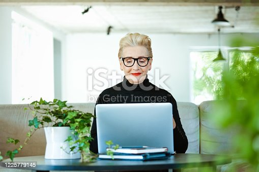 Home office concept. Portrait of elderly elegant lady wearing black turtleneck and glasses smiling at camera. Confident senior businesswoman having video conference on laptop, working at home.
